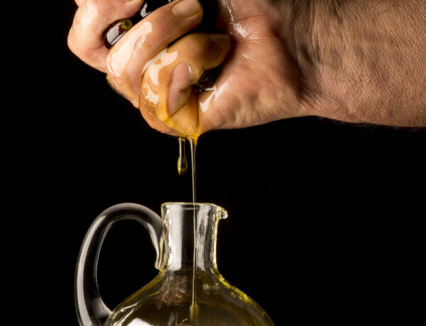 Hand squeezing oil from olives