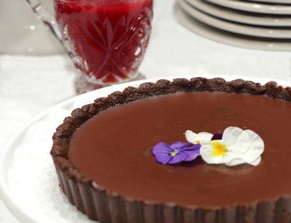 Chocolate tart garnished with edible pansies; pitcher of raspberry sauce to the side