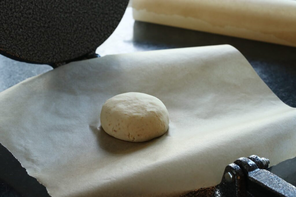 Cassava flour dough mound on tortilla press
