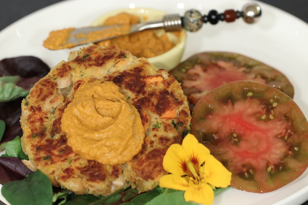 White Bean and Rutabaga Burgers served with heirloom tomatoes and romesco sauce