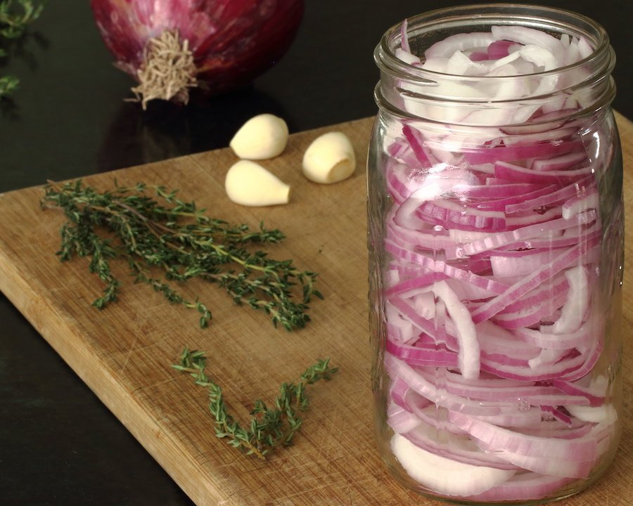 Red onions arranged in a quart size canning jar arranged with fresh thyme, 3 whole garlic cloves, and a whole red onion