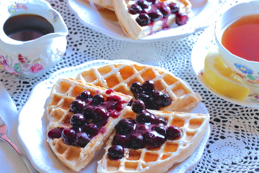 Plates of crispy gluten-free vegan waffles with blueberry sauce, herbal tea, and pitcher of maple syrup