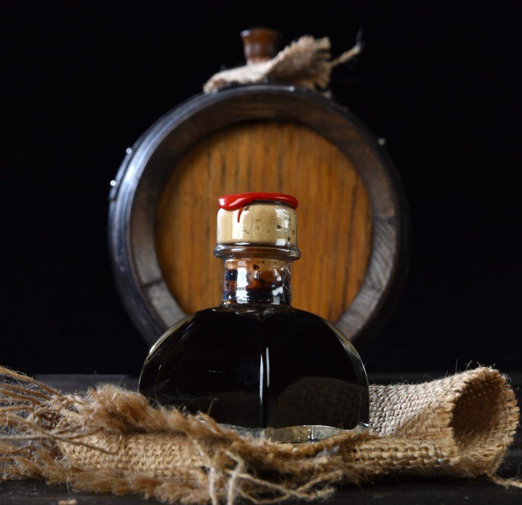 Small bottle of balsamic vinegar in front of barrell