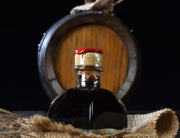 Small bottle of balsamic vinegar in front of barrell