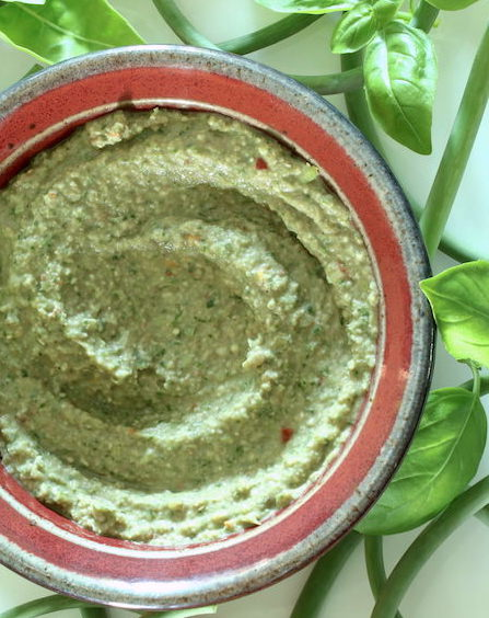 Oil-free vegan pesto in a small bowl against a white background with basil leaves and garlic scapes strewn around