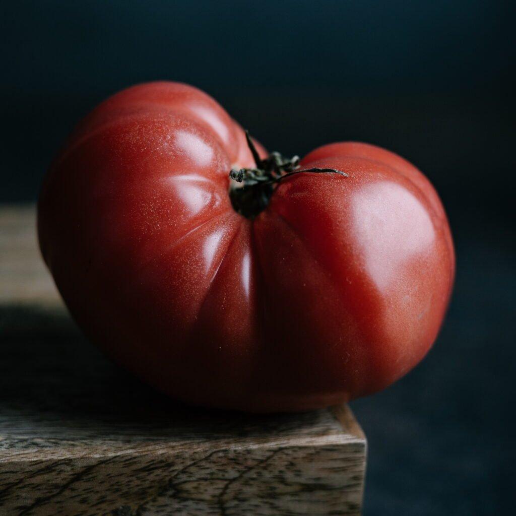 Single heirloom tomato against a dark background