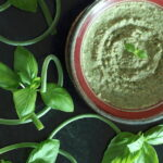 Bowl of Oil-Free Vegan Pesto surrounded by garlic scapes and basil leaves