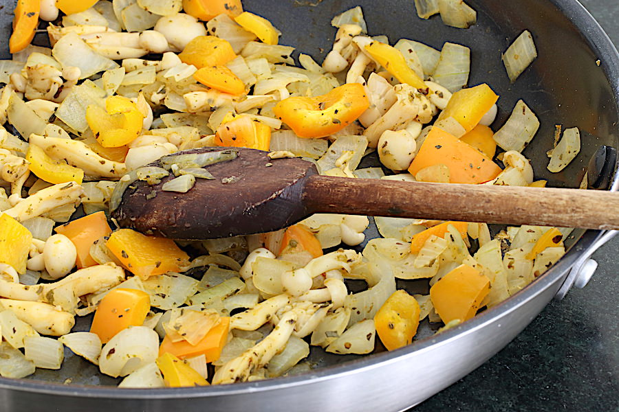 Broth sauteed onions, mushroom, peppers in a skillet being stirred with a wooden spoon