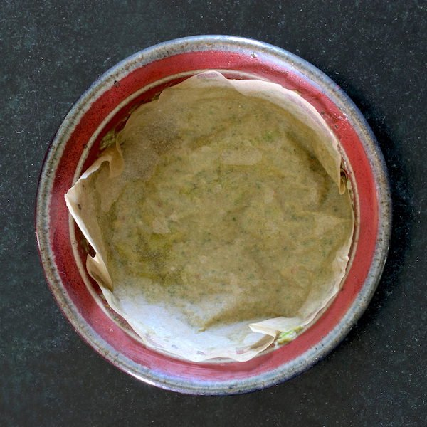 Oil free vegan pesto leftovers in a small bowl covered with parchment paper.
