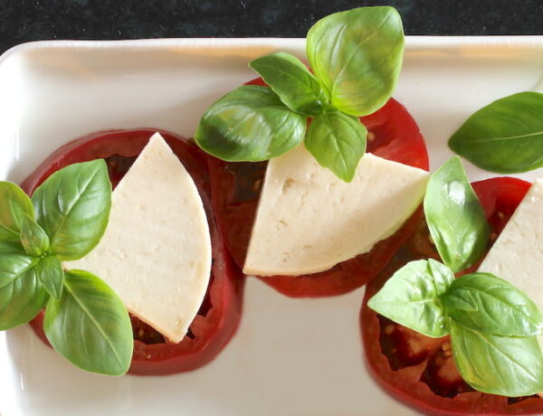 Three tomato slabs with cashew cheese and basil