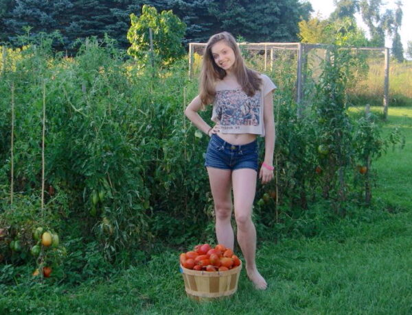 Our daughter Laura standing in front of our tomato garden with a basket of picked tomatoes