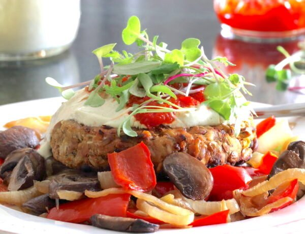 Vegan burger served over mushrooms, onion, and peppers; slathered in creamy dressing with a garnish of sprouts