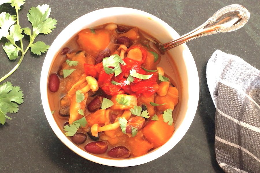 Butternut Squash Chili in a bowl with sprig of cilantro t the side
