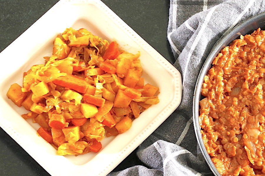 Ethiopian cabbage and potato stew served on a small square plate, with glimpse of spicy red lentils in a pan