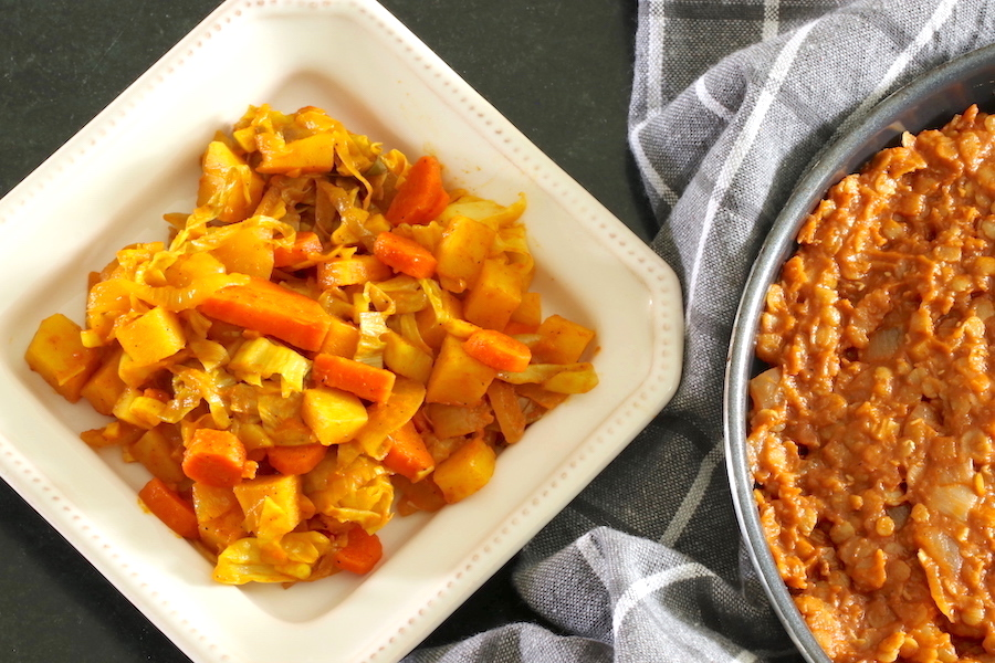 Ethiopian cabbage stew served on a square plate with a glimpse of spicy red lentils stew