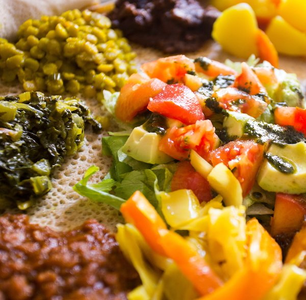 Ethiopian vegan platter including Atakilt Wat served on Injera flatbread