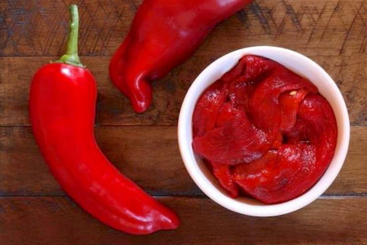 Two fresh red peppers arranged around a small bowl of roasted red peppers