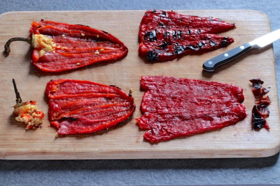 Roasted red peppers with seeds and stems removed laying on cutting board