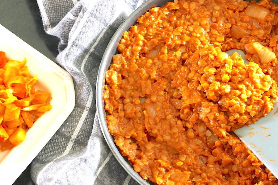 Ethiopian spicy red lentils in skillet with glimpse of Ethiopian cabbage stew