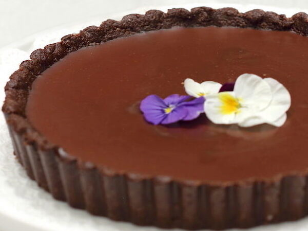 Close up chocolate tart with fresh flowers arranged on top