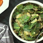 Ethiopian style collard greens in a bowl with a glimpse of spicy lentils to the side