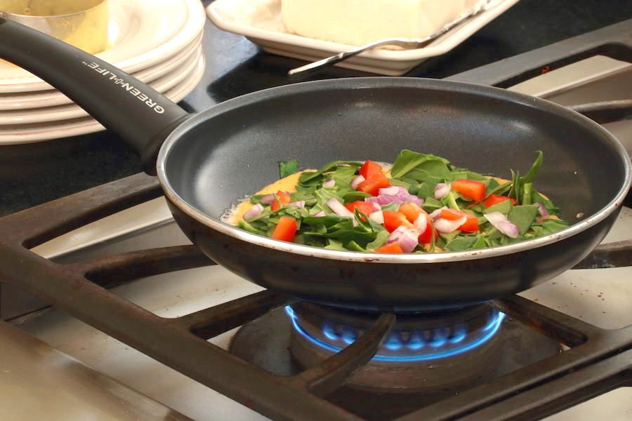 Omelette cooking in pan with veggies