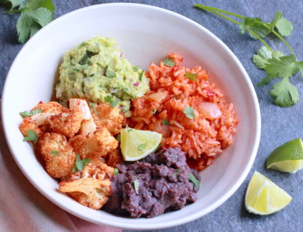 Cauliflower, guacamole, red rice, and black beans in a bowl