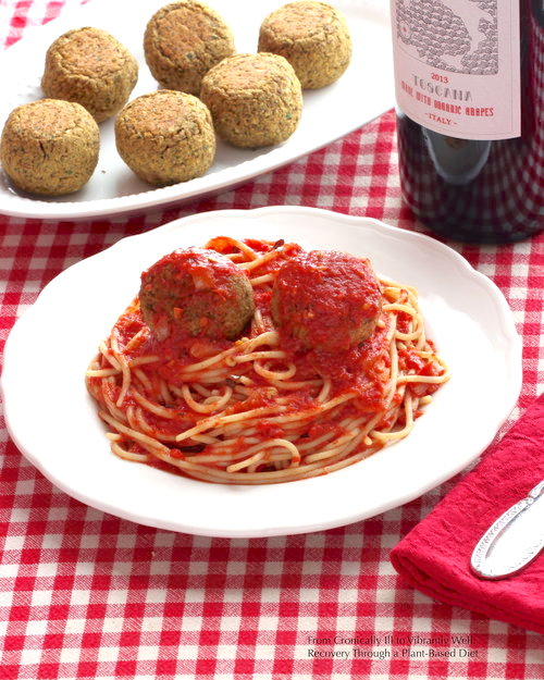 Plate of spaghetti dressed with marinara sauce and topped with two Lentil Balls; a plate of Lentil Balls in the rear