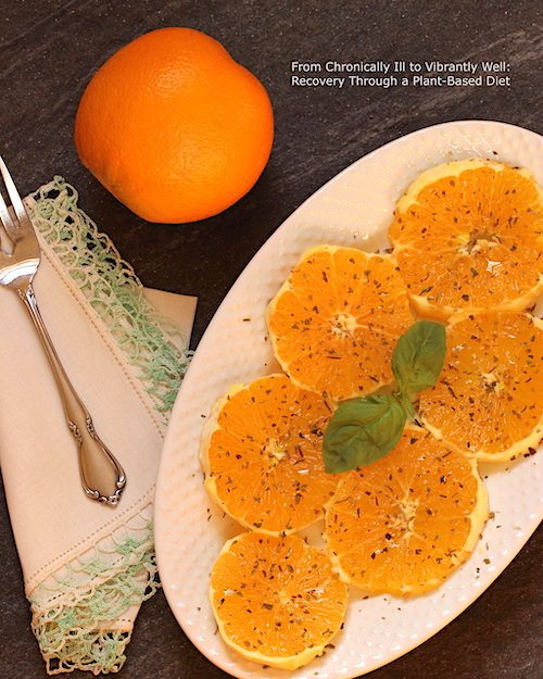 Orange Salad served on an oval plate with a napkin and fork to the side; an unpeeled orange in the background