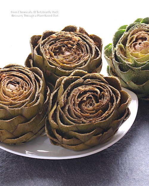 Three cooked Stuffed Artichokes sitting on a dish; one uncooked artichoke in the background