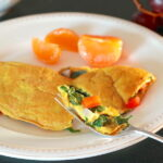 Forkful of Vegan Omelette highlighted with rest of omelette, mandarin orange sections, and grapes in background