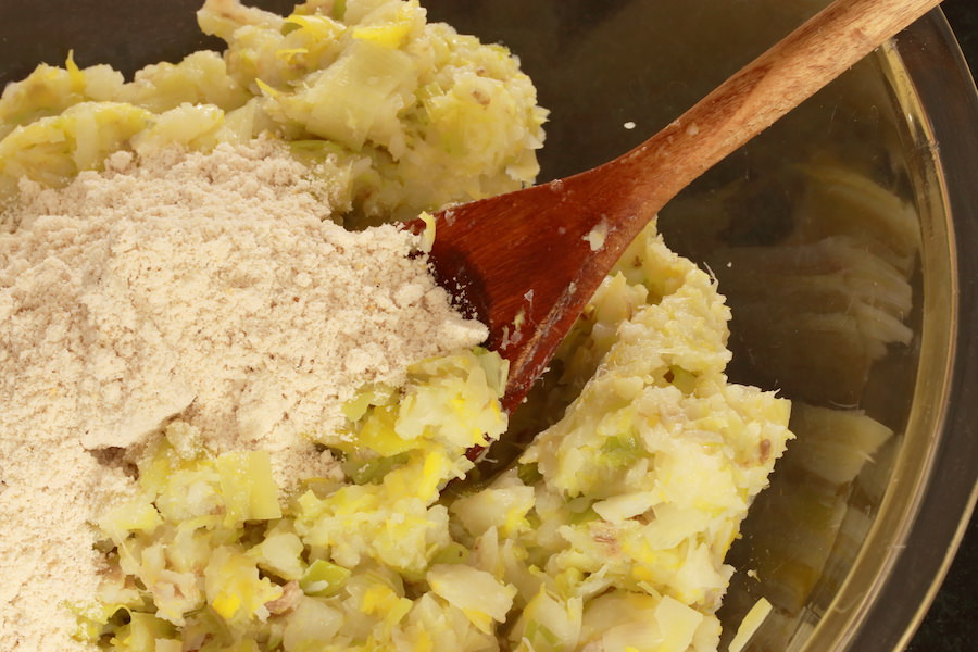 Cooked potatoes and leeks rough chopped; dry ingredients poured on top ready to be mixed