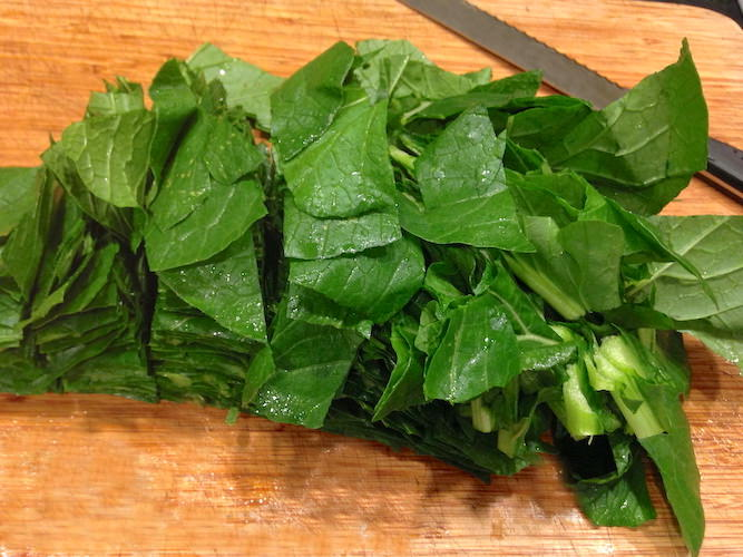 Mustard greens on a cutting board being cut up using large knife