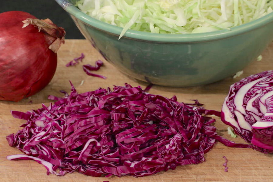 Bowl of shredded green cabbage with shredded red cabbage on cutting board in front