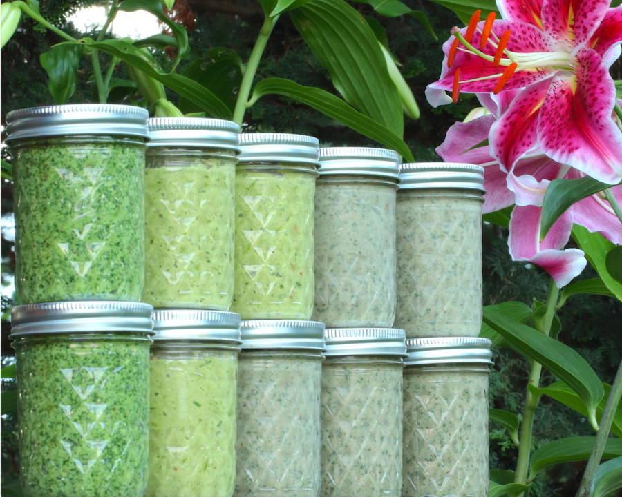 Three varieties of homemade pesto in pint-sized jars lined up