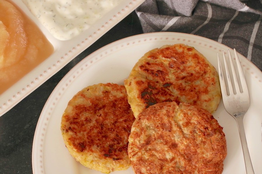 Three Vegan Potato Pancakes with Leeks plated; apple sauce and tzatziki sauce in the background and a checkered napkin to the side