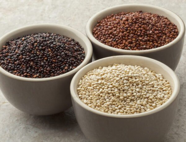 Three bowls containing white, black, and red quinoa