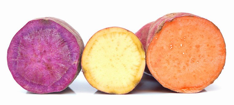 Purple, yellow, and orange sweet potatoes in a row