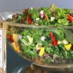 Kale and Chickpea Salad in a large clear glass bowl with a bottle of white balsamic vinegar to the side