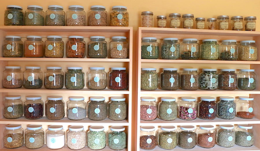 Over 50 half gallon jars filled with dry herbs arranged on pine shelving