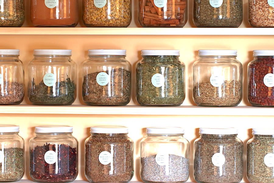 Close up of several half gallon jars filled with dry herbs and arranged on shelves