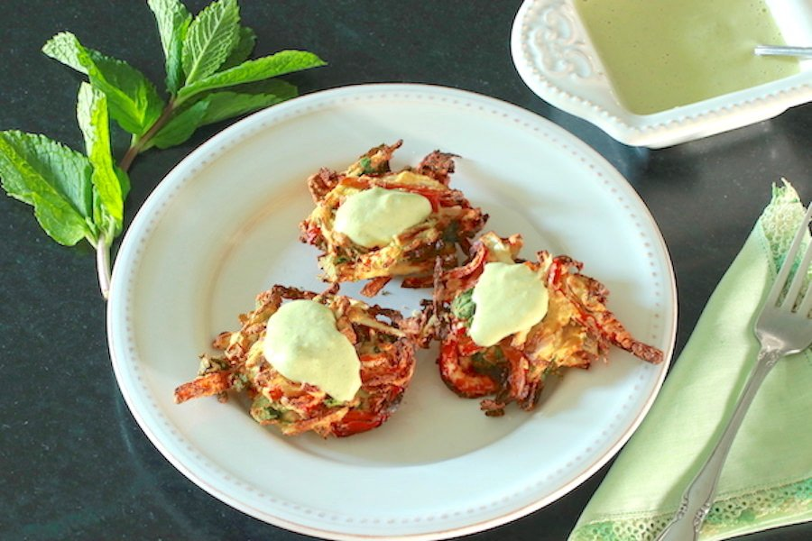 Three cooked pakora topped with Creamy Cashew Sauce and Dressing with a sprig of mint leaves to the side