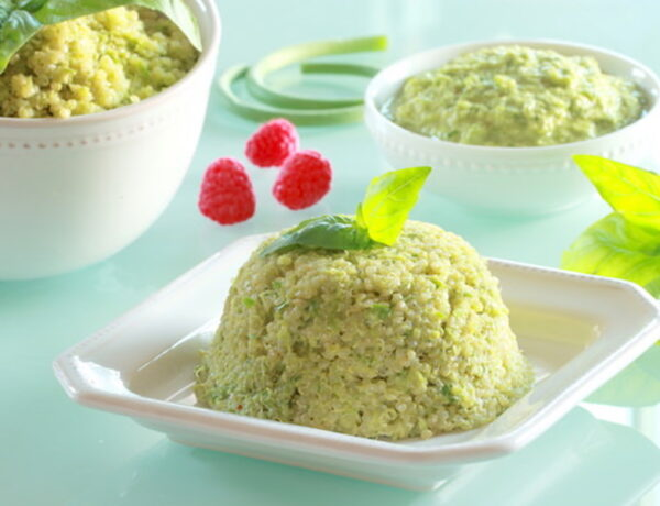 Pesto mixed into quinoa and formed into a mold; a bold of quinoa pesto and a small bowl of pesto in the distance