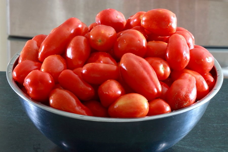 Roma tomatoes in a stainless steel bowl