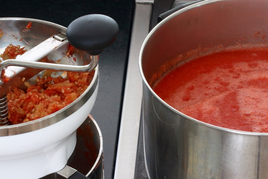 Glimpse of tomato skins being removed using a food mill, and glimpse of tomato puree being boiled down